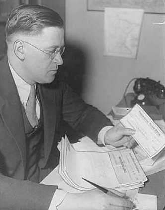 Black and white photograph of Elmer Benson at his desk, c.1934. Photographed by the St. Paul Daily News.