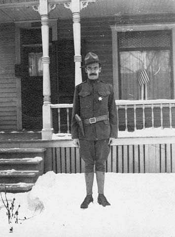 Black and white photograph of A. A. Baker, member of the Minnesota Home Guard, 1917. The star he wears designates him as a special deputy sheriff sworn in during the Streetcar Workers Strike.