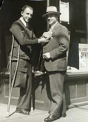Black and white photograph of Congressman Melvin Maas (right) with a disabled constituent, 1930.