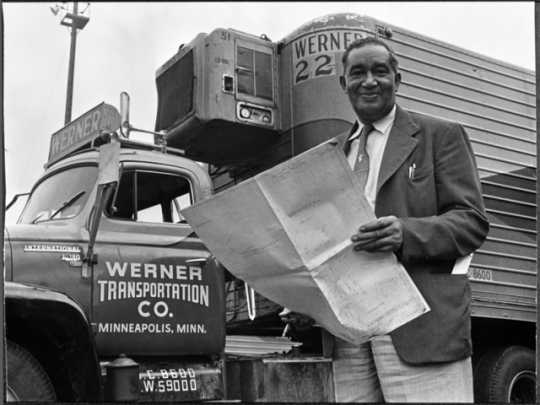 Black and white photograph of Frederick McKinley Jones standing next to a truck outfitted with a mobile refrigeration unit, c.1950.