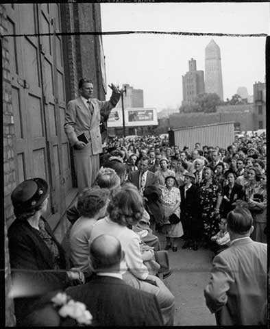 Photograph of the Reverend Billy Graham speaking at the stage door of the Minneapolis Auditorium.