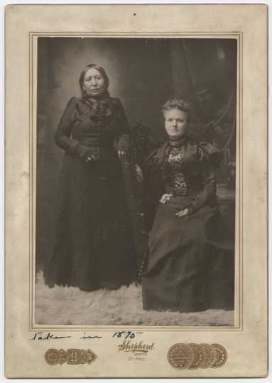 Mary E. Schwandt Schmidt (Mrs. William) and Snana Good Thunder (Maggie Brass), 1899. Photo by Shepherd Photo Studio.