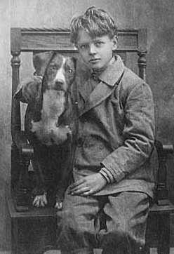 """Black and white photograph of Charles Lindbergh with his dog """"Dingo,"""" c.1912."""
