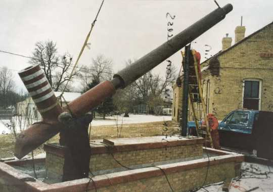 Color image of the world's largest peace pipe, photographed during installation next to the Rock Island Depot in Pipestone, 1998.