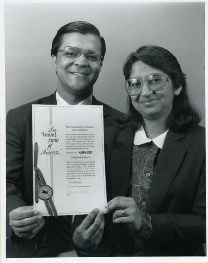 Black and white photograph of Sam (Smarajit) and Sumita Mitra, a husband-and-wife team of 3M research scientists, display their U.S. patent for copolymerizable UV stabilizers, 1987.