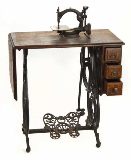 Noiseless Automatic Sewing Machine designed by by the Willcox & Gibbs Sewing Machine Company in London, England. The treadle and gears run smoothly on this chain stitch sewing machine. The machine is mounted on a wooden table with an iron base, a foot treadle, and three drawers.