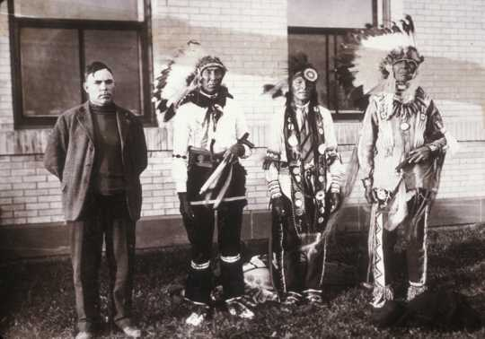 Black and white photograph of a translator with three Ojibwe men. The Ojibwe leader Miskogwan (Red Feather) stands on the far right. Northwest School of Agriculture Dedication Day, October 5, 1920.