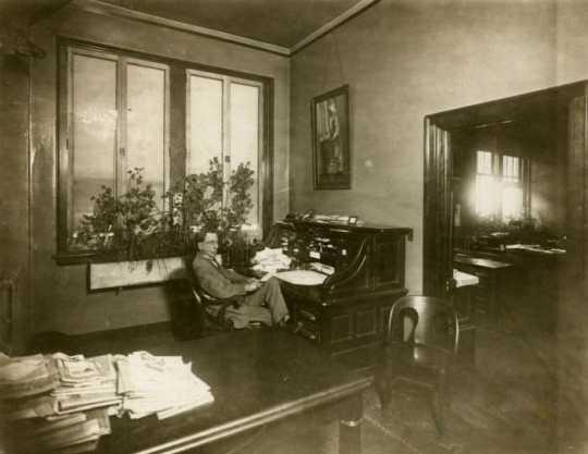 Black and white photograph of Swan Turnblad in his office at the Svenska Amerikanska Posten, ca. 1920.