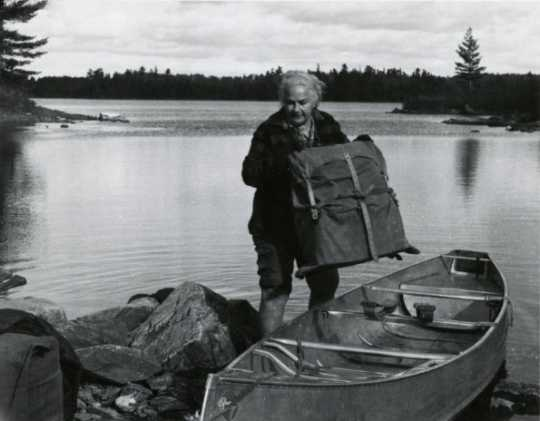 Black and white photograph of Dorothy Molter lifting a pack out of a canoe, Isle of Pines, Knife Lake, Boundary Waters Canoe Area, ca. 1960s.