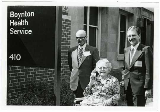 Ruth Boynton with colleagues Don Cowan and Paul Rupprecht at the ceremony where the University Health Service was renamed the Boynton Health Service. She is elderly and sitting in a wheelchair. The two men stand behind her and the sign with the name of the building is in the foreground.
