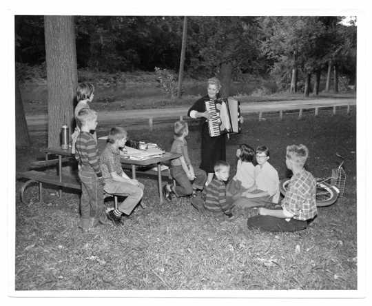 Knutson playing her accordion for a group of children in a park